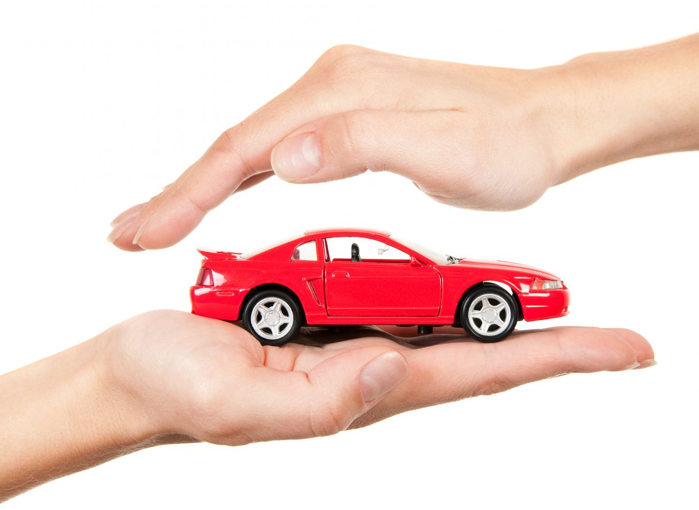 Red car in hands on a white background. Concept of safe driving